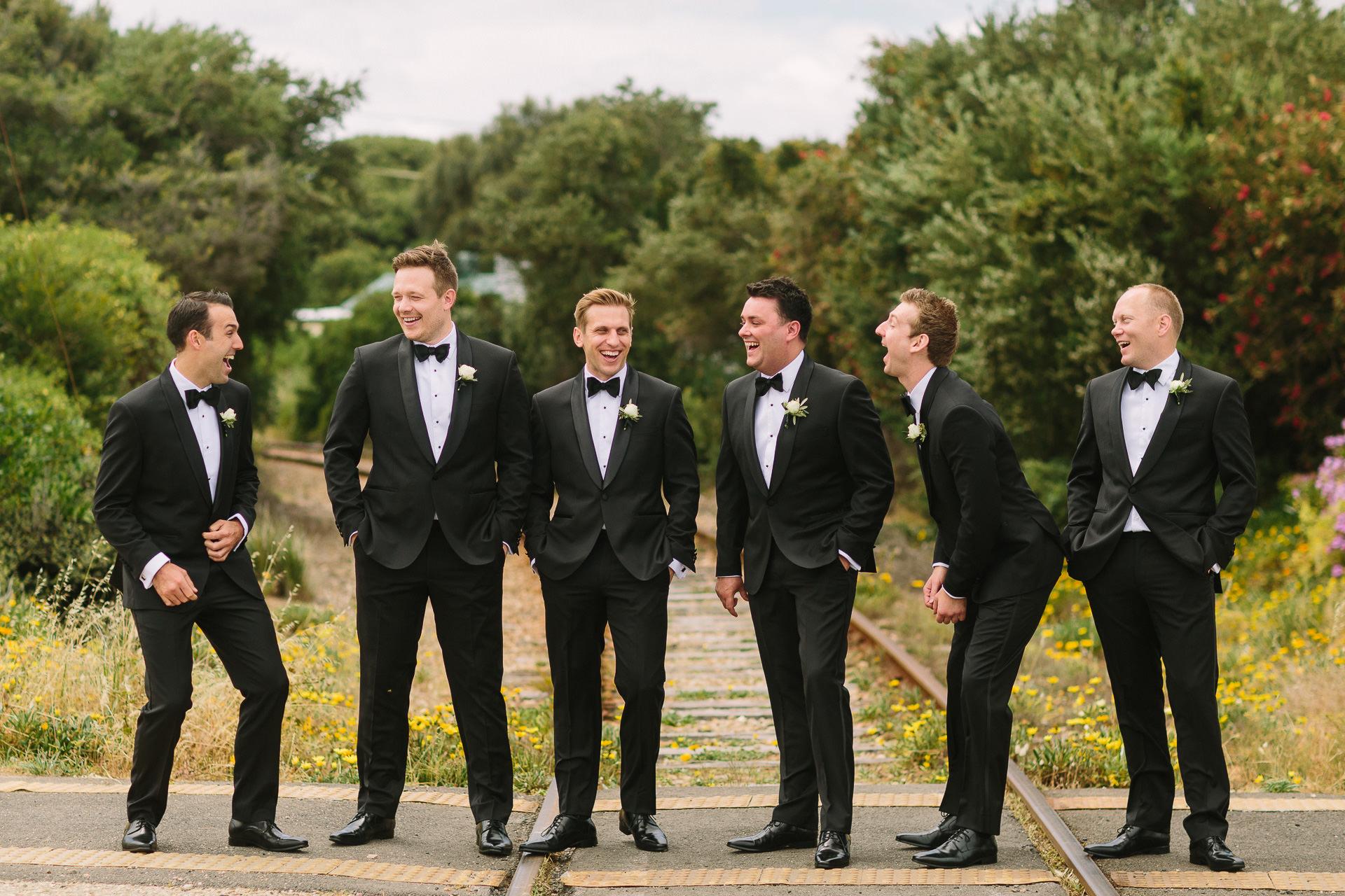 Port elliot wedding, dapper groom and groomsmen in black tie on train tracks