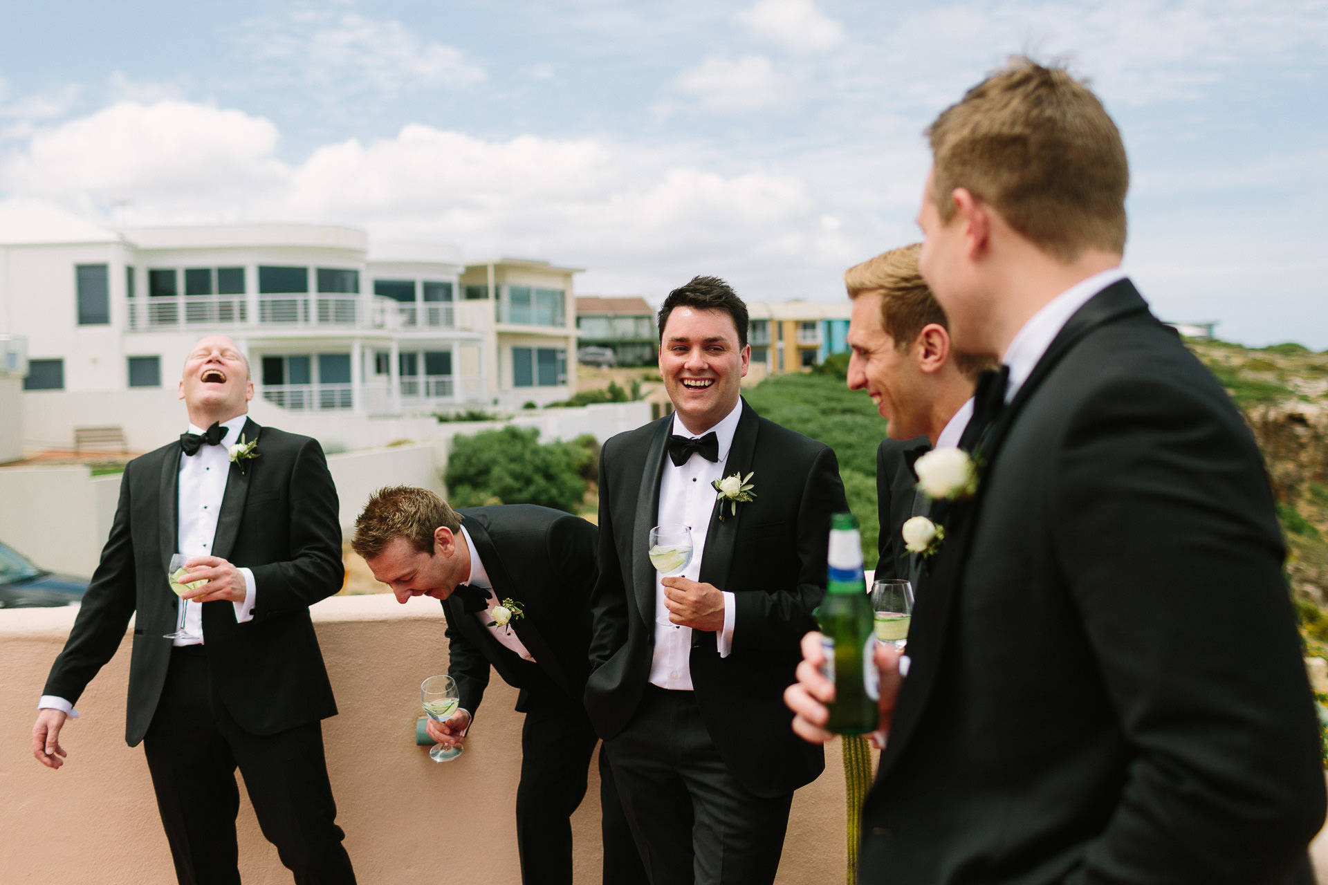 Groom and groomsmen laughing, having fun, drinking outside
