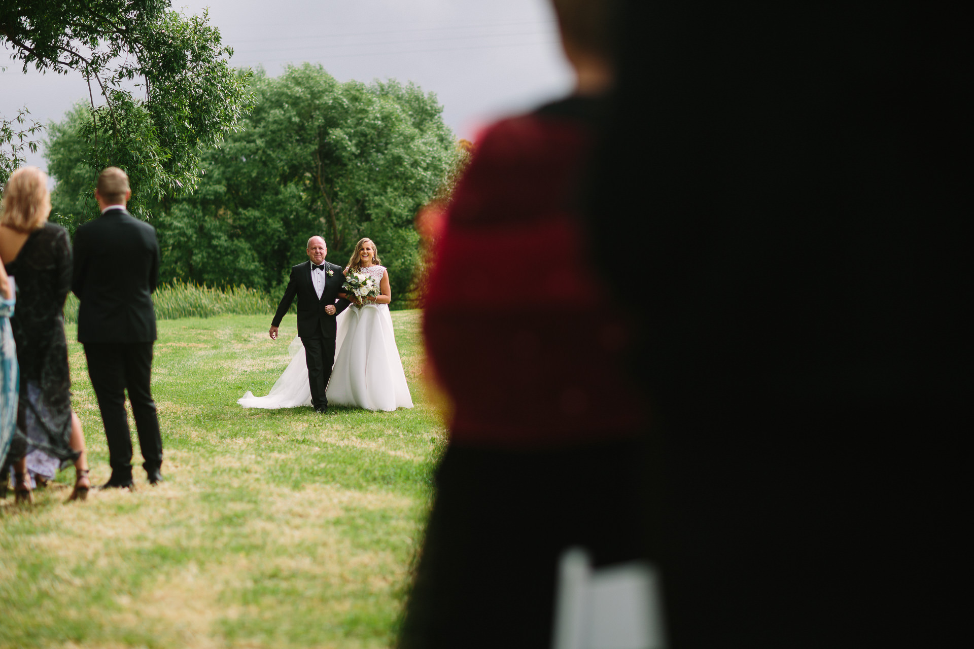 father and bride walk down aisle at Bolt Hoban estate in a garden ceremony