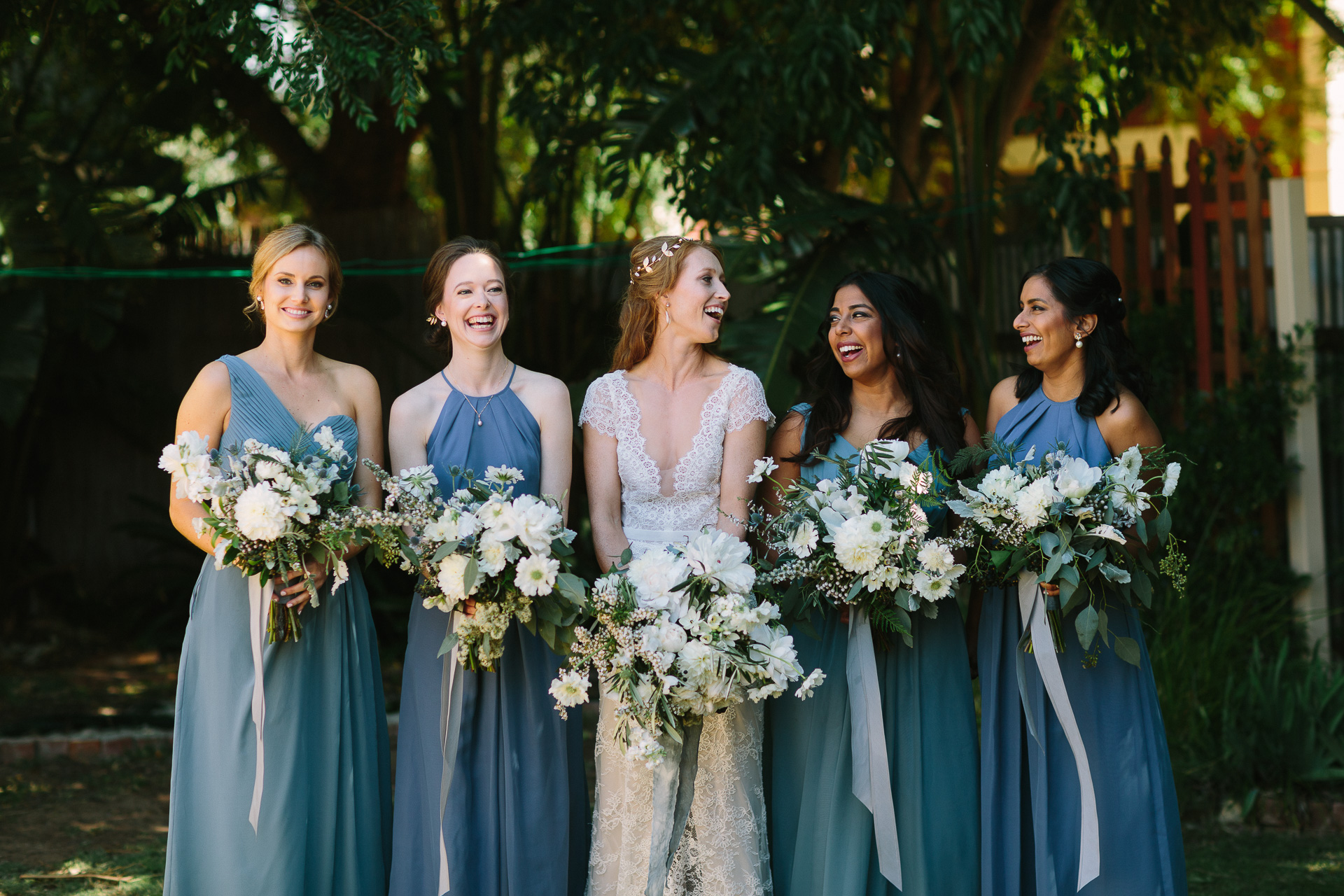bridesmaids laughing , blue dresses, poppies flowers in garden
