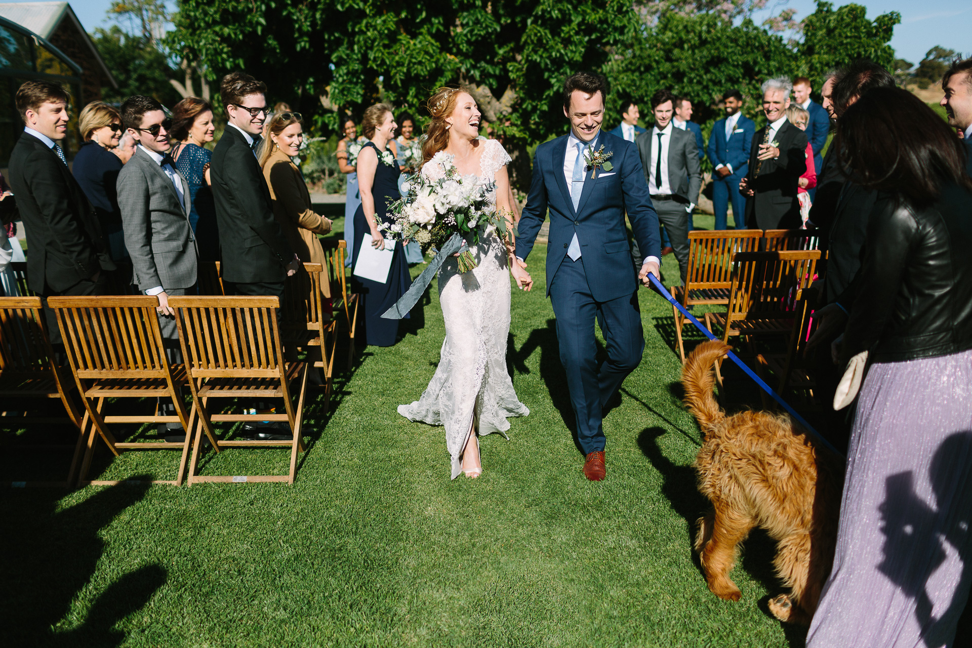 Coriole winery wedding mclarenvale, bride and groom walking down aisle with their dog