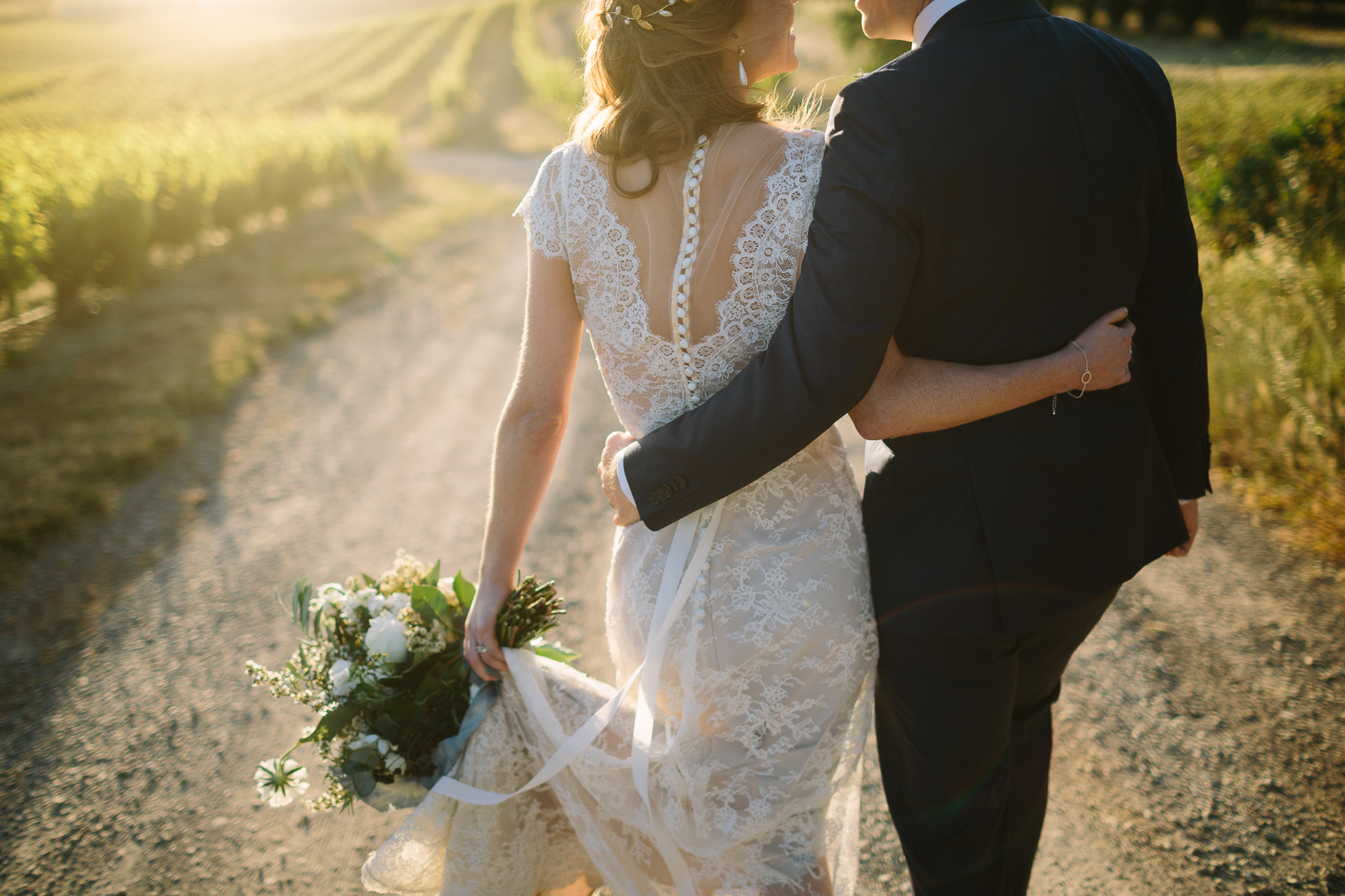 bride and groom in vineyard with flowers and back of dress detail , buttons, lace , flowercrown