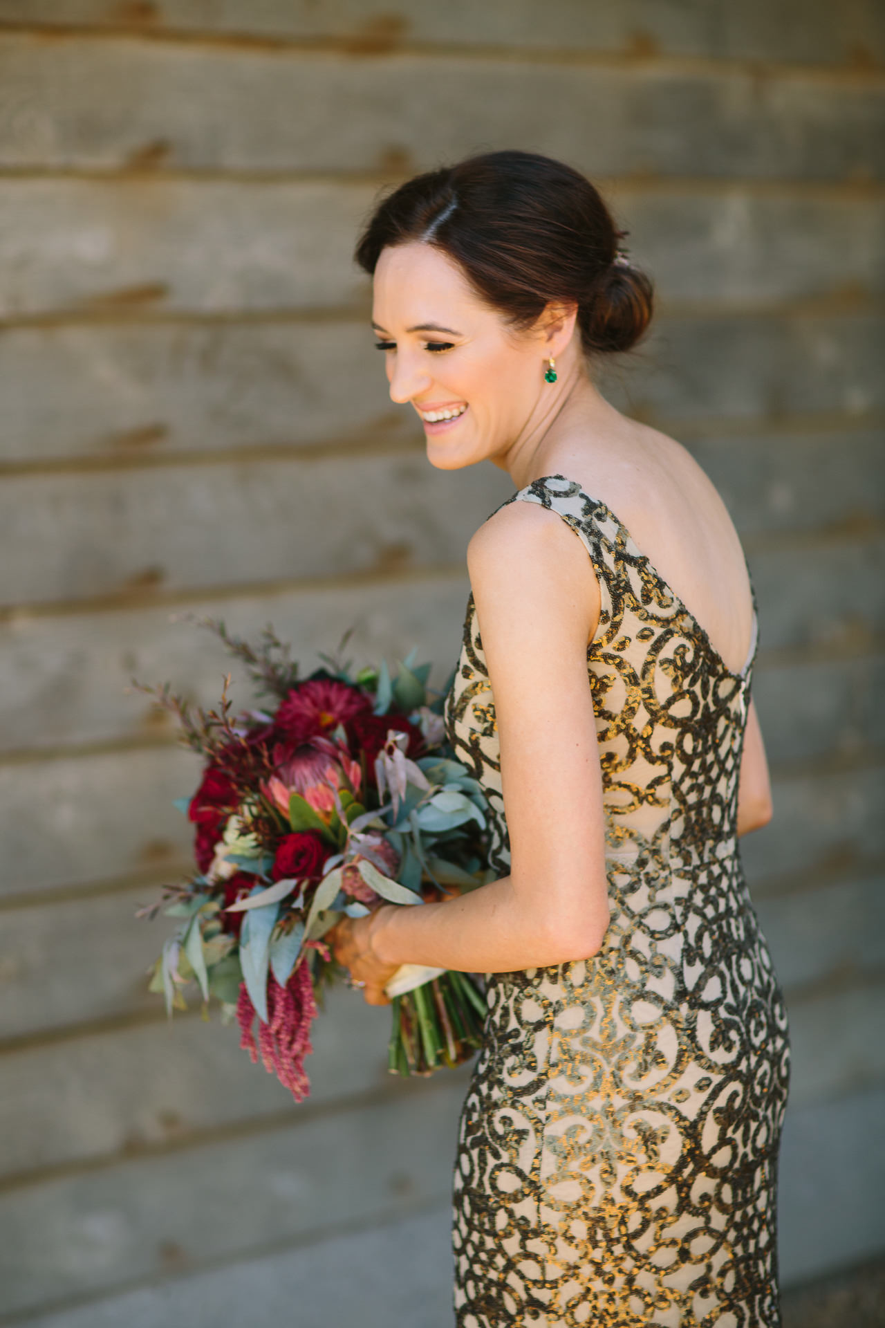 Bride laughs naturally as she holds her flowers