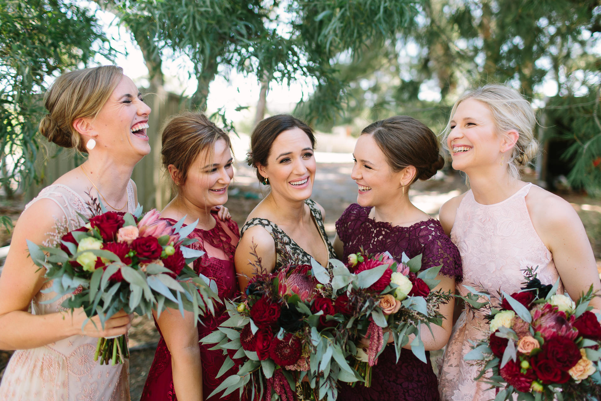 Bridesmaids laugh together with bouquets and mismatched dresses