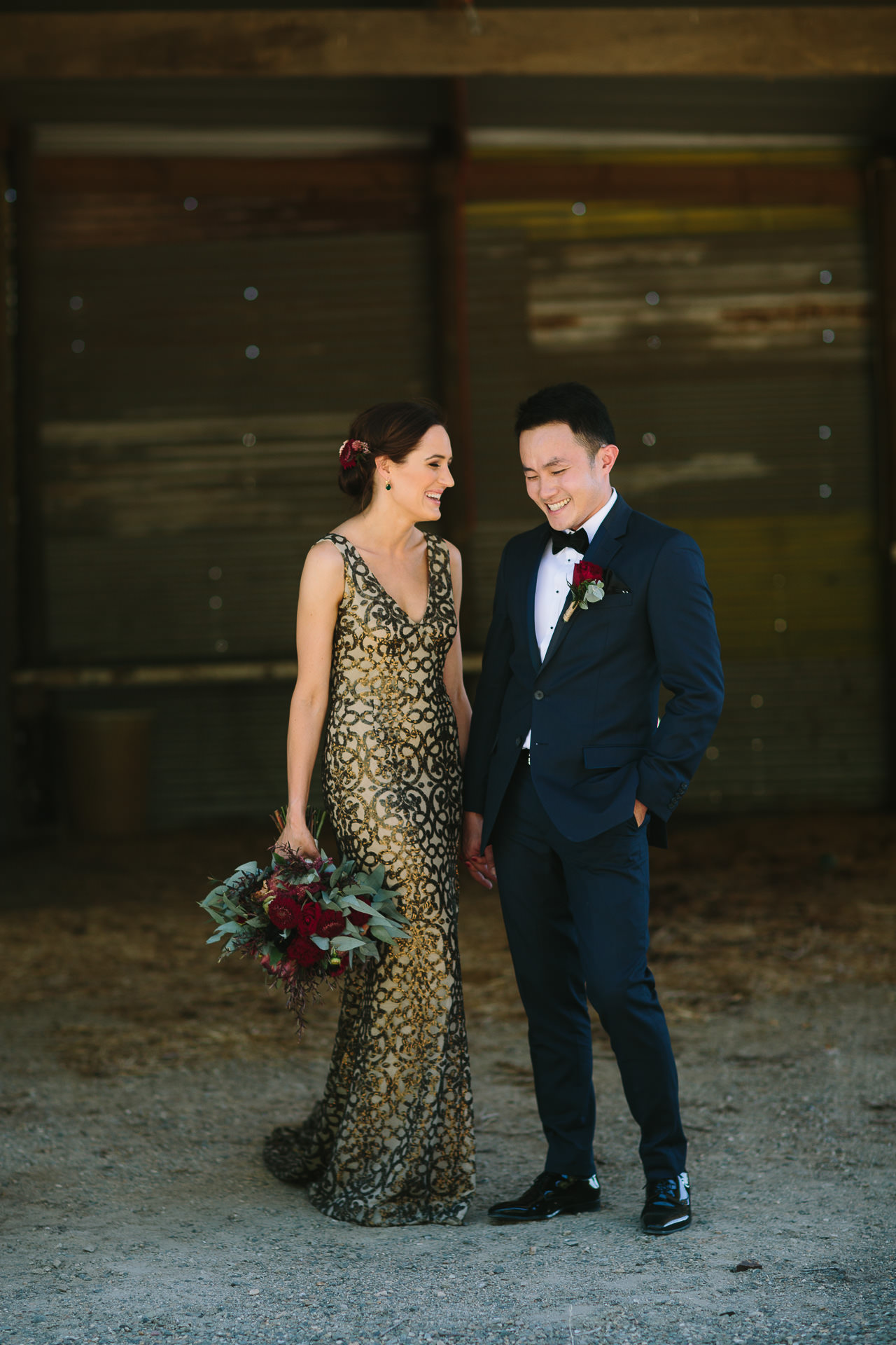Dapper groom and stylish bride hold hands smile together at One Paddock wedding Currency Creek