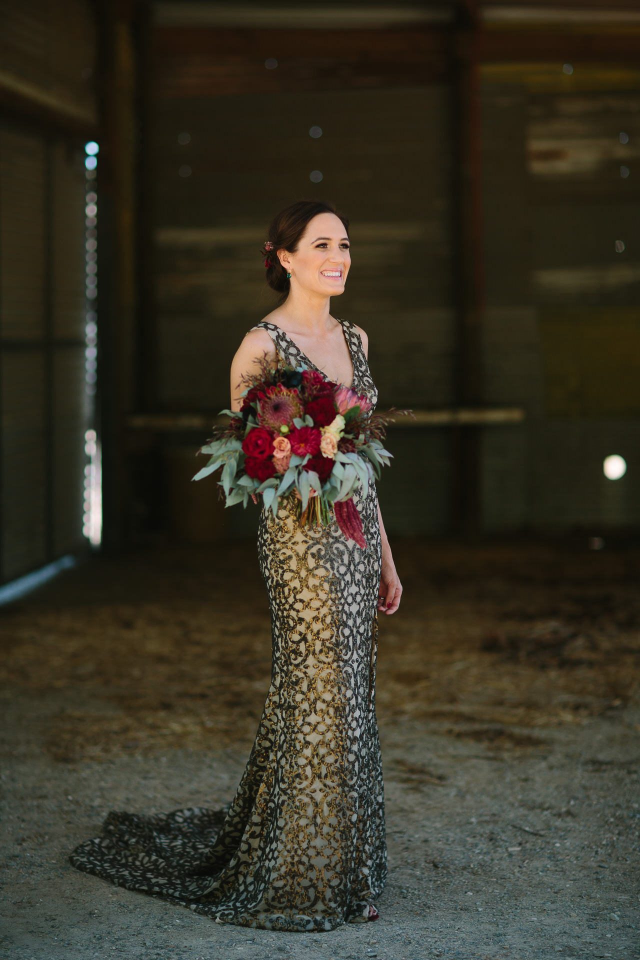 Bride poses with flowers and gold wedding dress