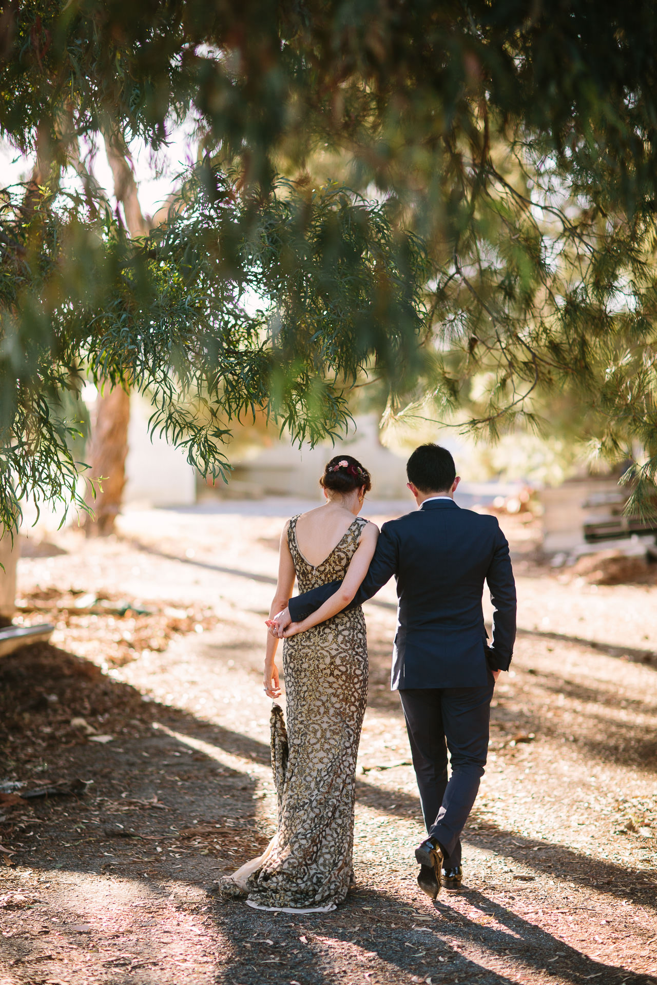 Stylish bride and groom walk away hand in hand at One Paddock wedding