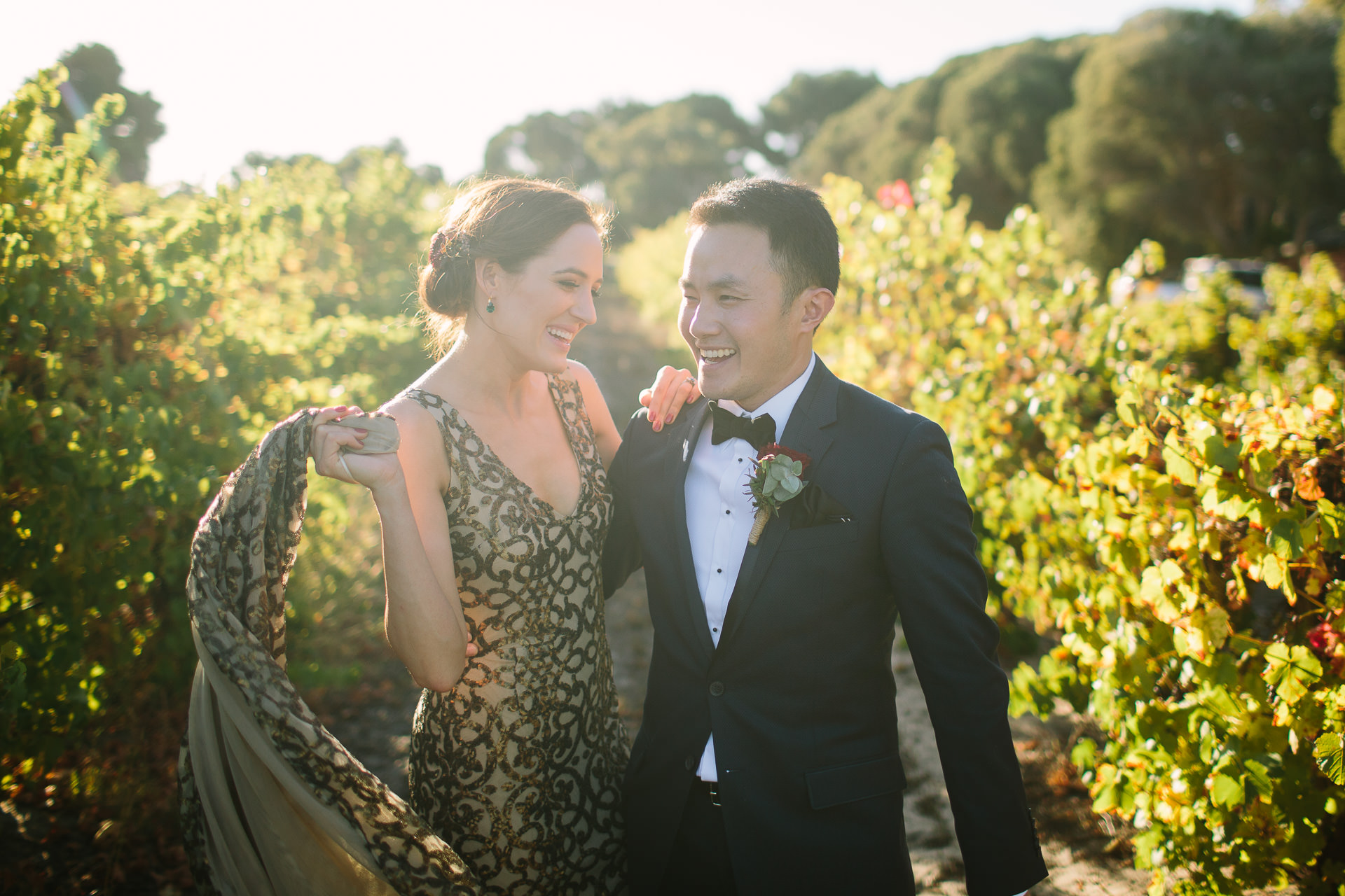 Bride and groom laugh together in Vineyard at One Paddock wedding
