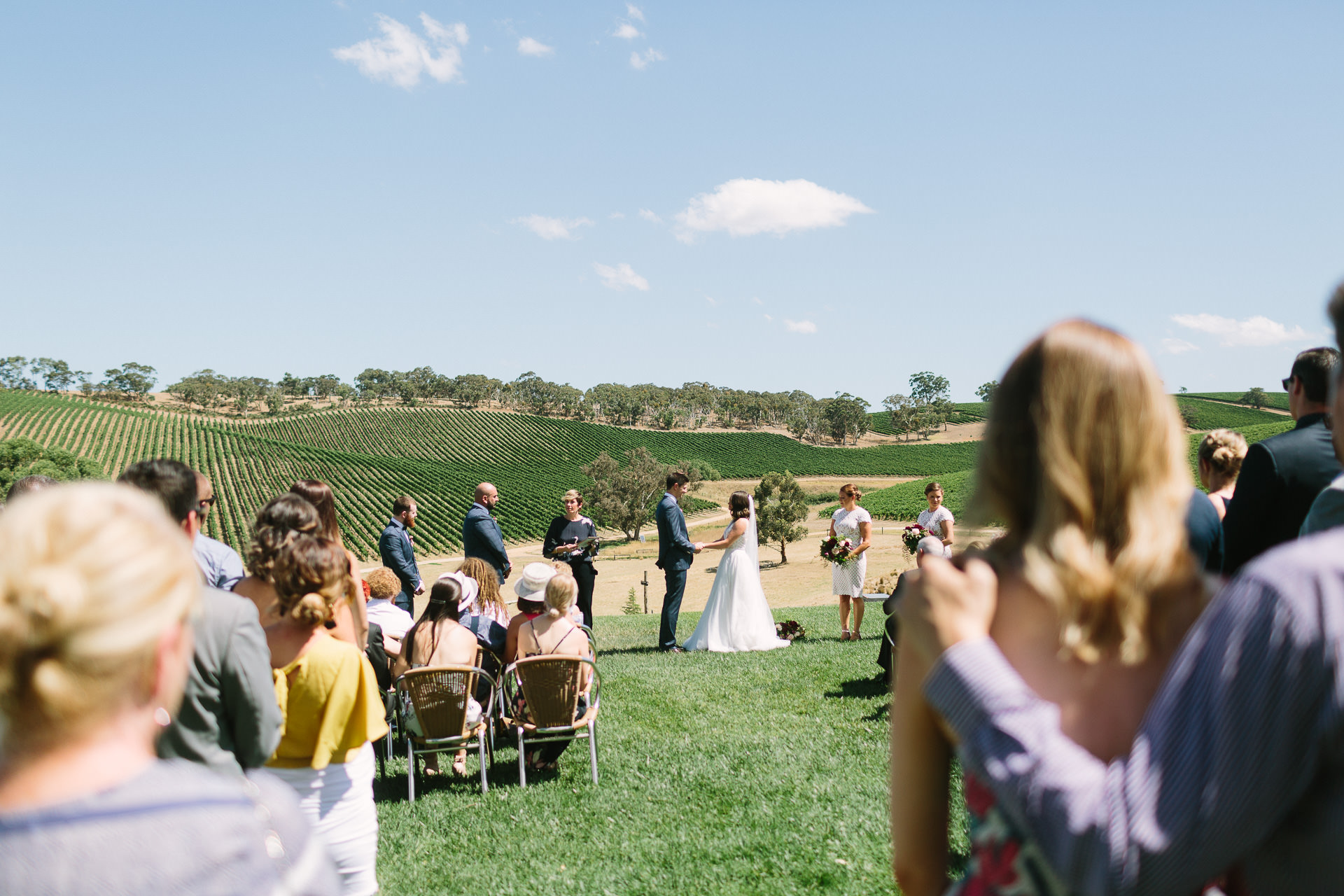 Longview winery wedding ceremony on lawn with sweeping vineyard views