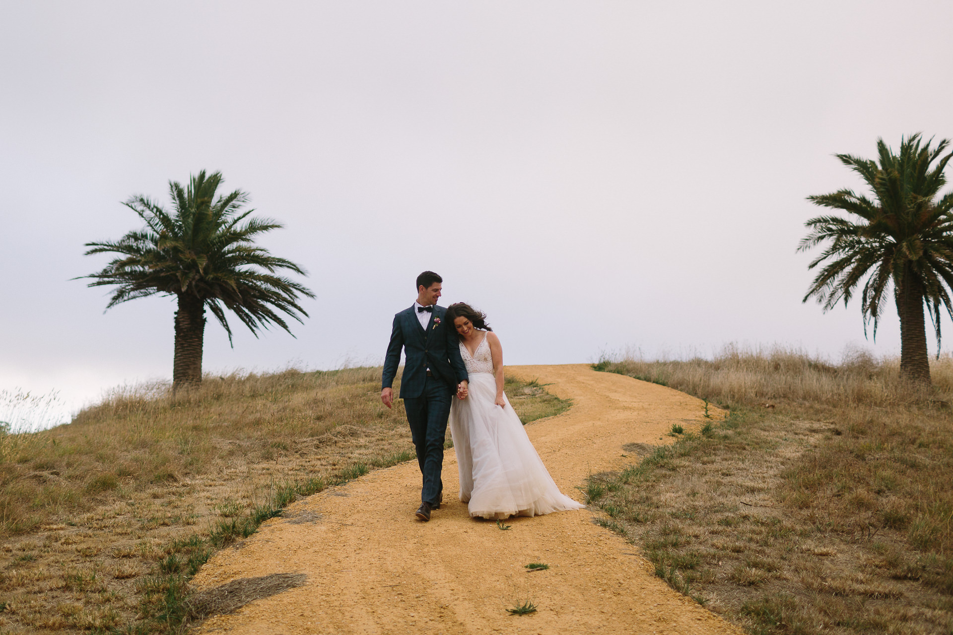 Bride and groom wander between the palm trees at Longview vineyard following their wedding ceremony