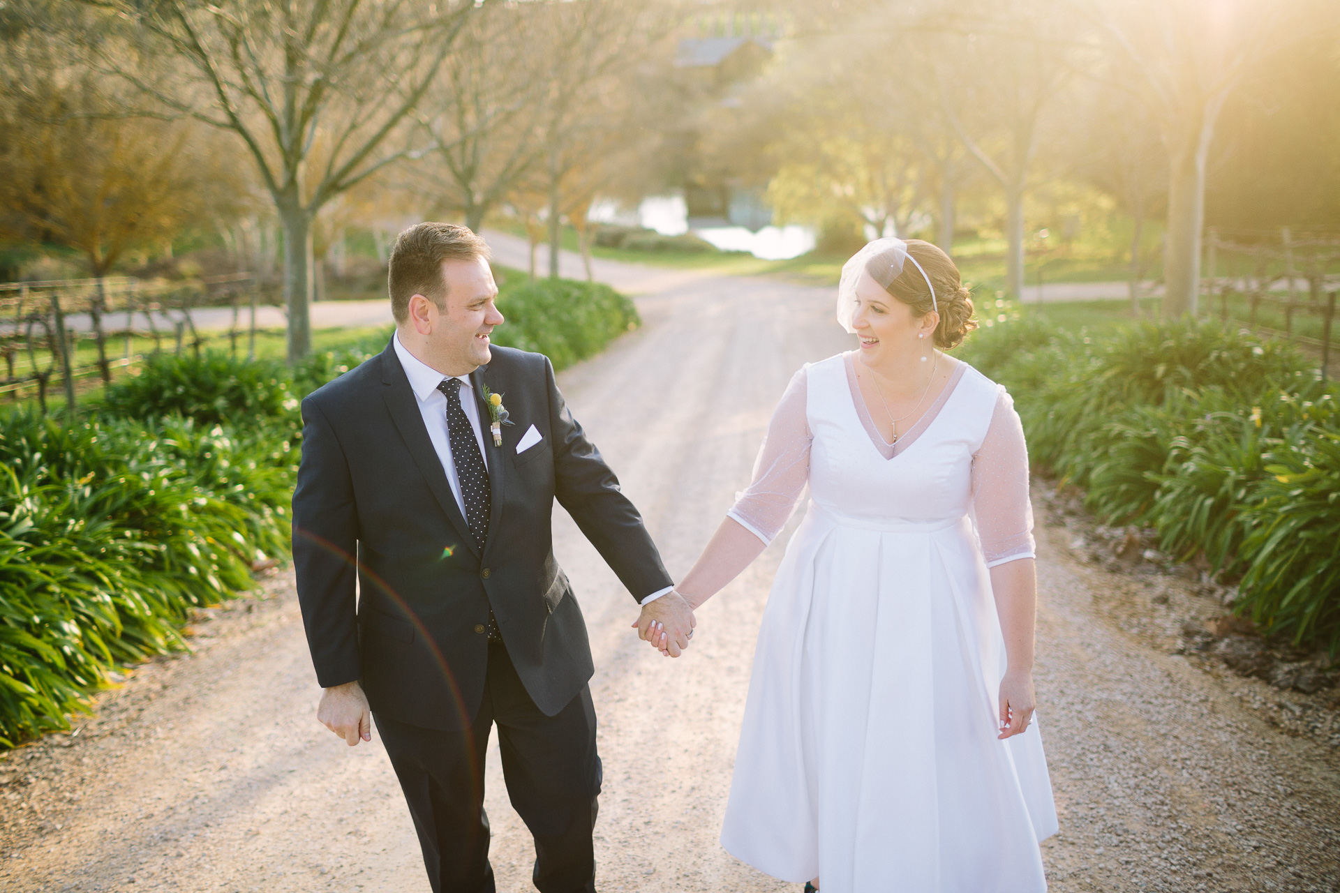 Happy bride and groom at their wedding at K1 winery, walking hand in hand along backlit tree lined driveway