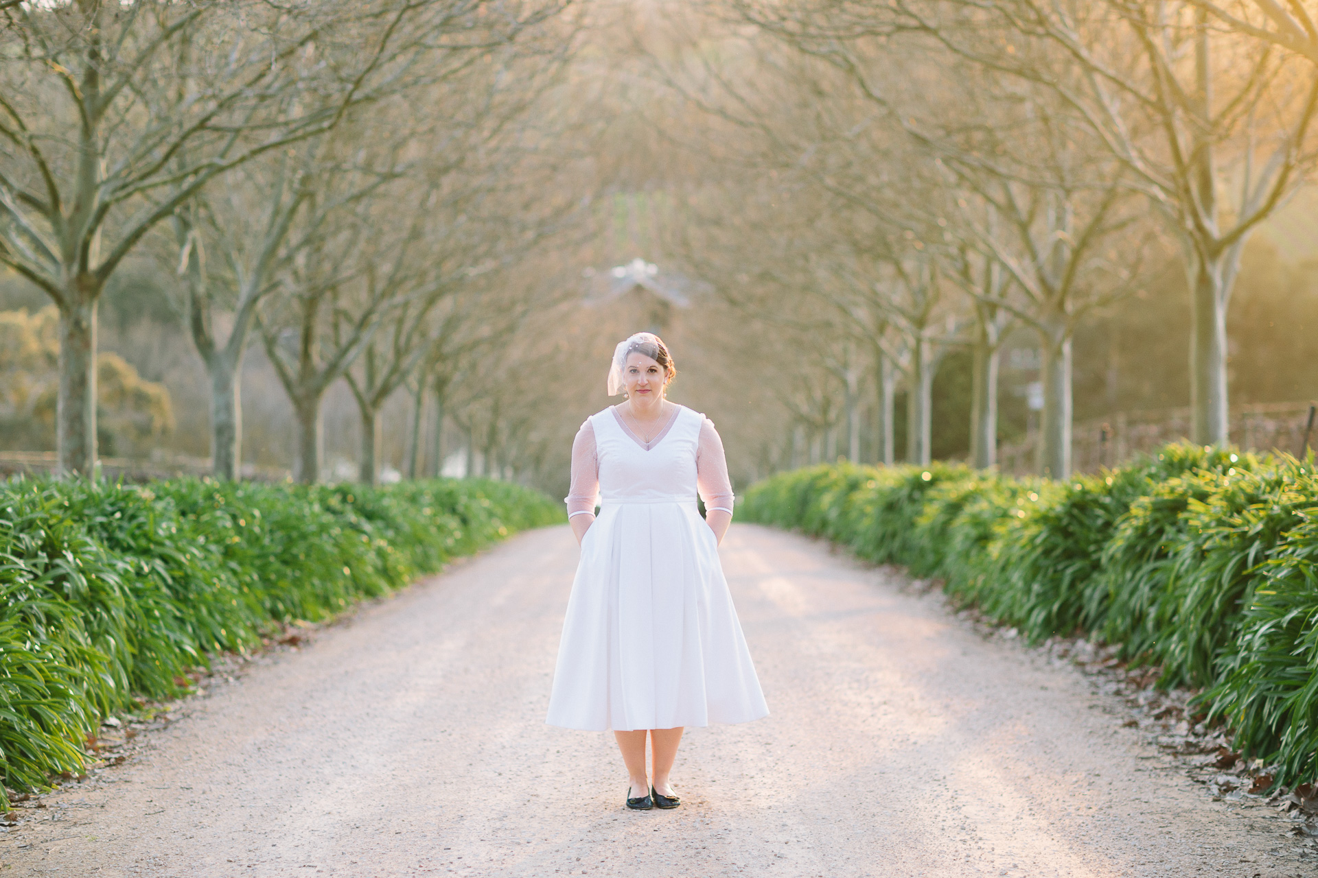 portrait of bride in wedding dress with long sleeves and fascinator on tree lined driveway at K1 winery near Kuitpo forest